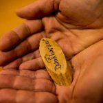 Hände mit Holzschild